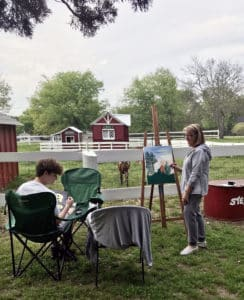 A lady and young man paint with easels while looking at a meadow and small barn