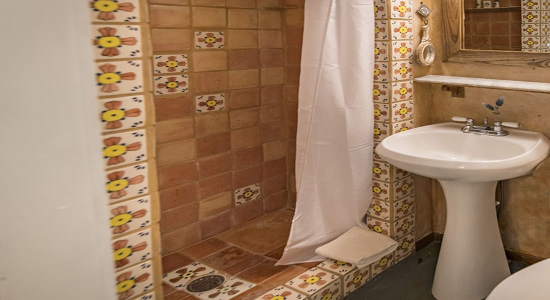 A tile shower with white pedestal sink