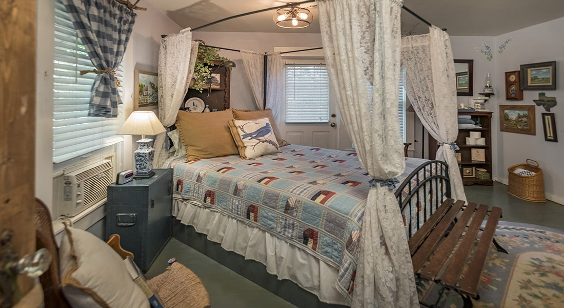 A blue and white quilt on iron bed with lace curtain corners and rug on floor