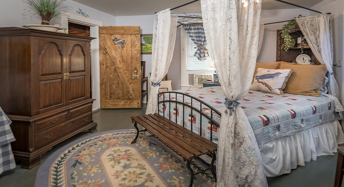 Blue and white quilt on iron bed with lace corners with wooden door and antique armoire in background