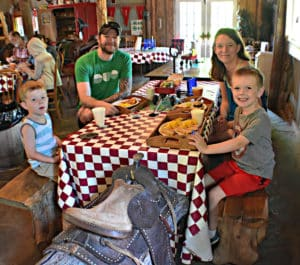 A family of four sits around a checkered table in a barn eating breakfast