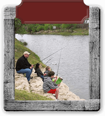 Wooden frame around a photo of a man and three children fishing in the river.