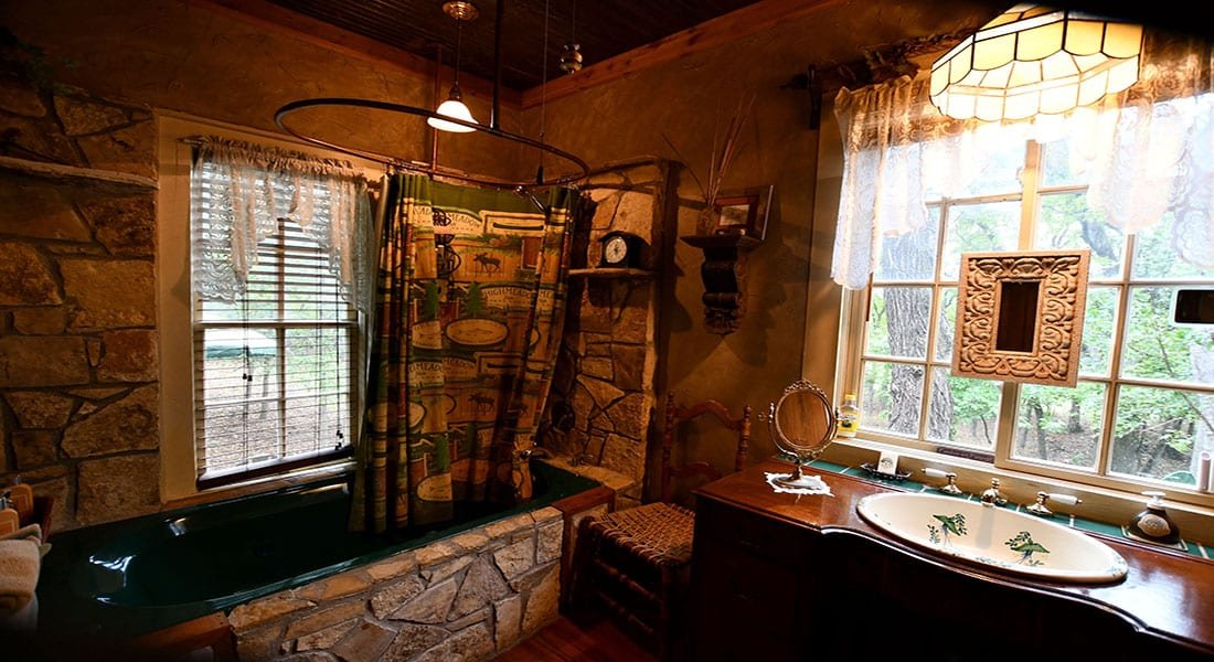 A green jacuzzi bathtub with wooden surrounding walls and antique sink with windows behind it showing trees