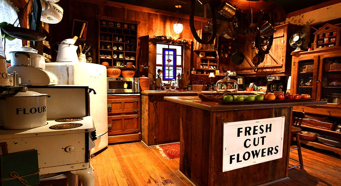 A wooden floor with wooden kitchen island with large sign saying Fresh Cut Flowers and antique stove