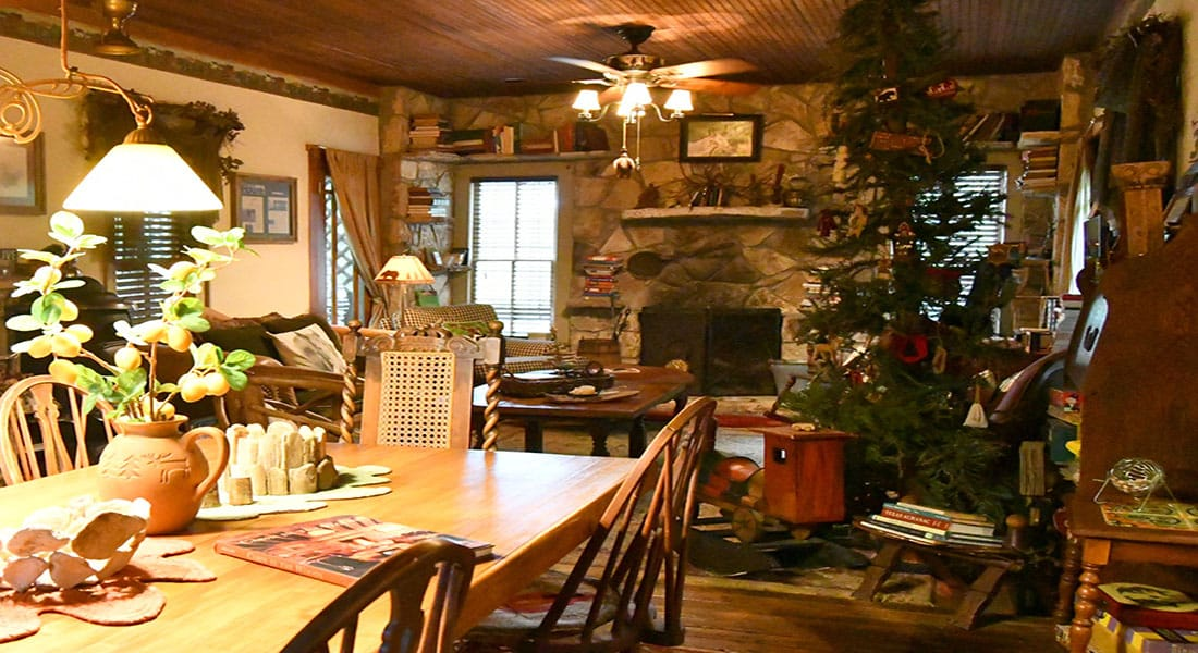 A stone fireplace with wooden dining table and rustic decor