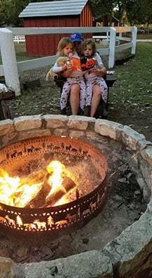 A dad holds two young twin daughters in his lap reading a book to them by a campfire.
