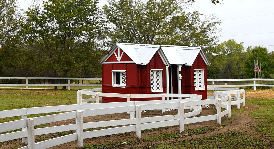 Red and white small cabin with white wooden fence is children's library