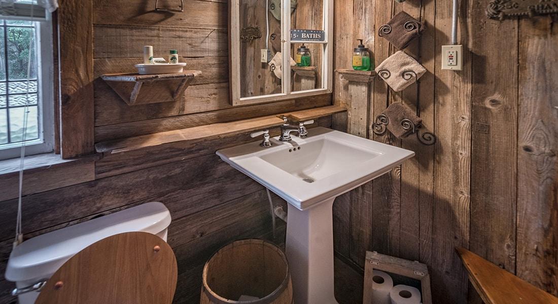 A white sink with mirror in a farmhouse bathroom
