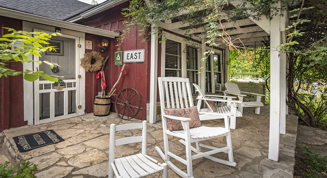 White rocking chairs sit on a stone porch in front of a red farm house