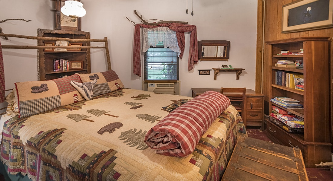 A queen bed with nature quilt and check bedroom with farmhouse decor