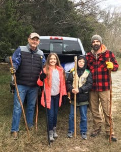 Family of 4 stands with walking sticks in winter apparel