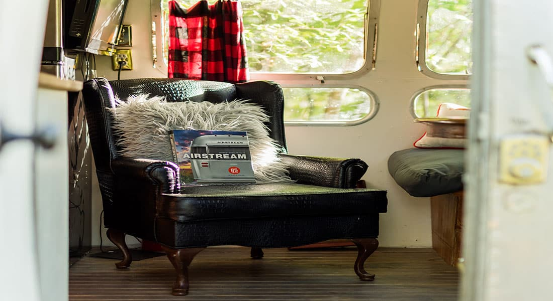 A black leather chair with grey fluffy pillow sits in front of a window with red and black check curtains