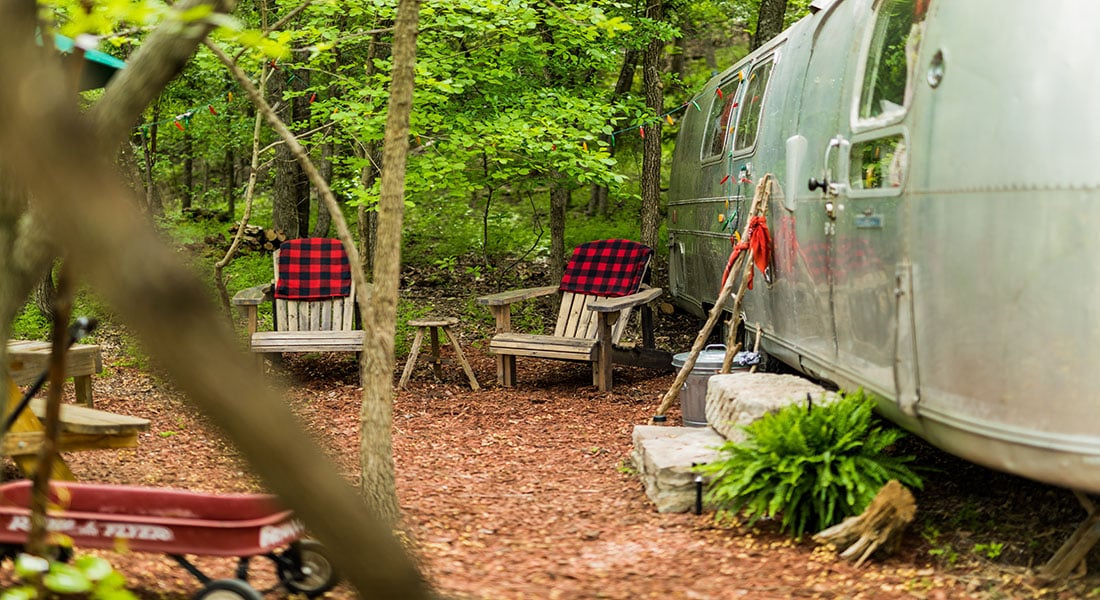 Wooden adirondack chairs with red and black check blankets sit outside a silver Airstream trailer in a private picnic area surrounded by trees
