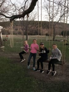 4 pre-teen girls sit in swings hanging from a tree while holding hotdogs around a campfire