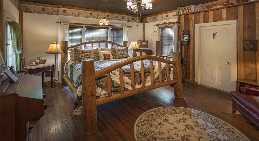 A large wooden king size bed with horse quilt and wooden floor