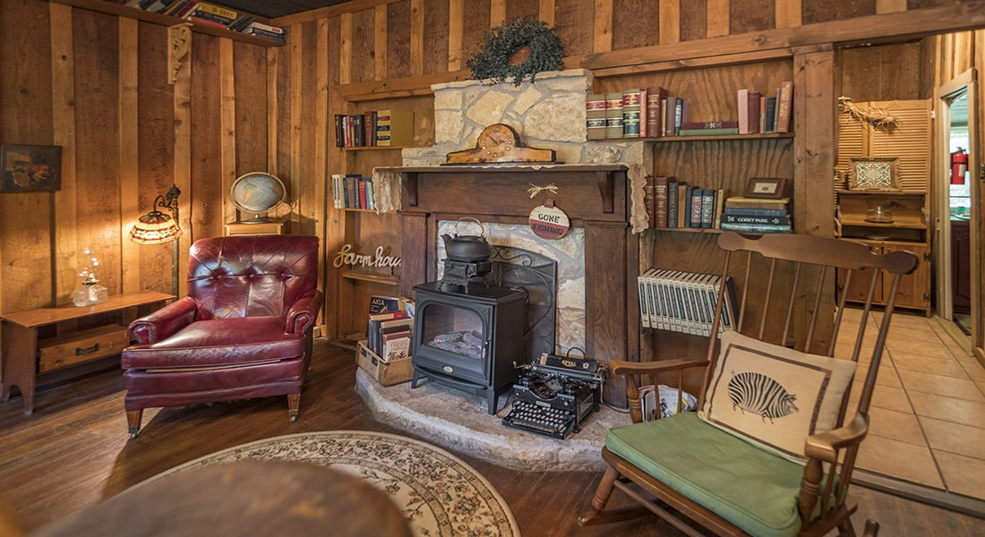 A fireplace mantle with stone hearth, leather chair and antique farmhouse decor