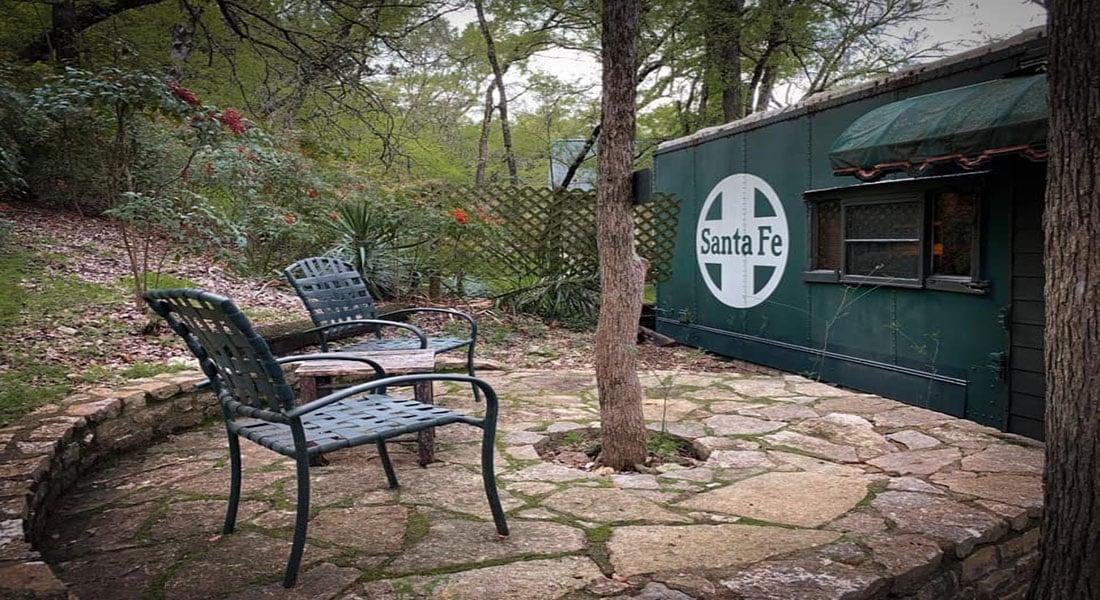 A rock terrace with chairs sits behind a Santa Fe Rail Car cabin