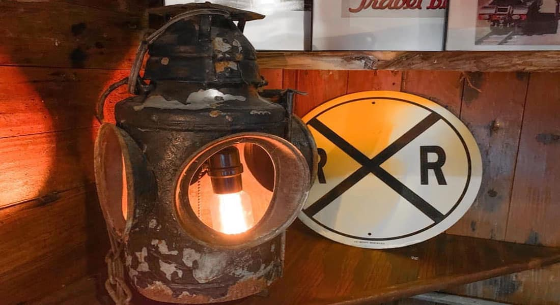 An antique lantern made into a lamp sits beside a railroad crossing sign