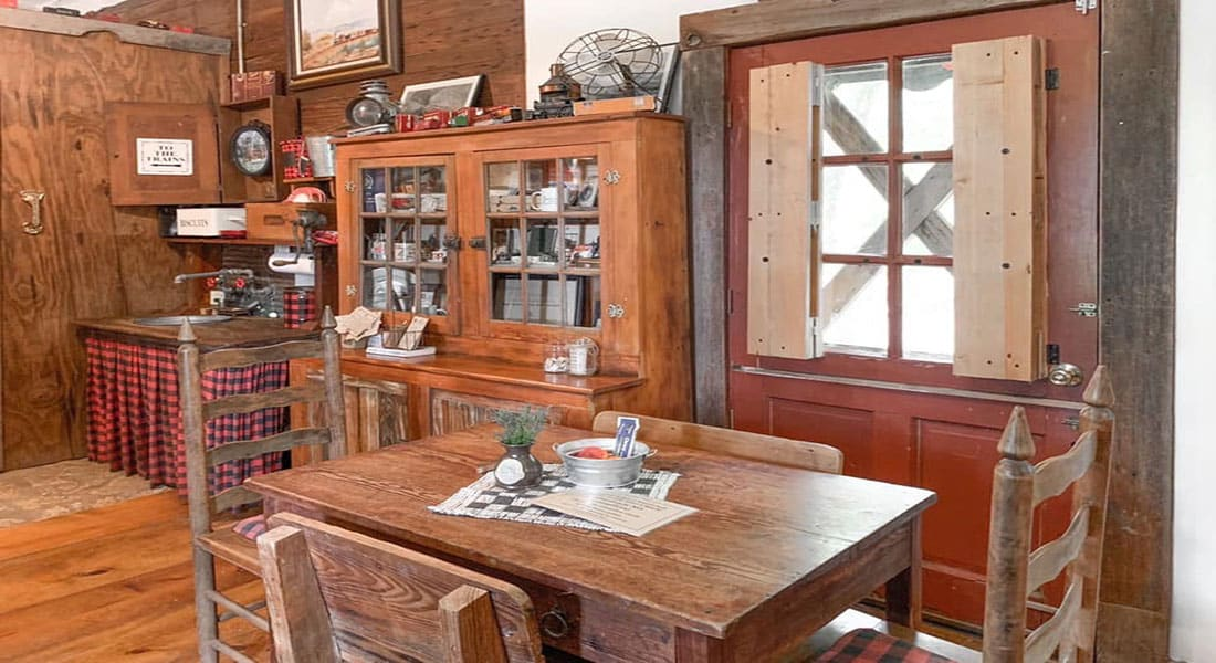 A wooden dining table with chairs and antique curio cabinet and train decor
