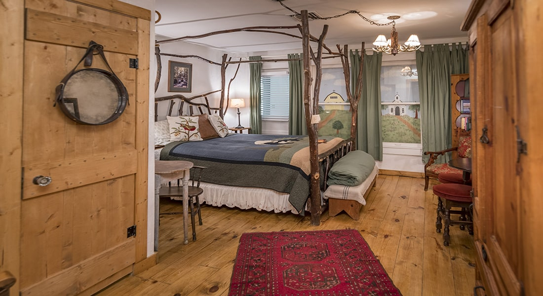 A wooden floor bedroom with a tree branch bed with bear and nature quilt