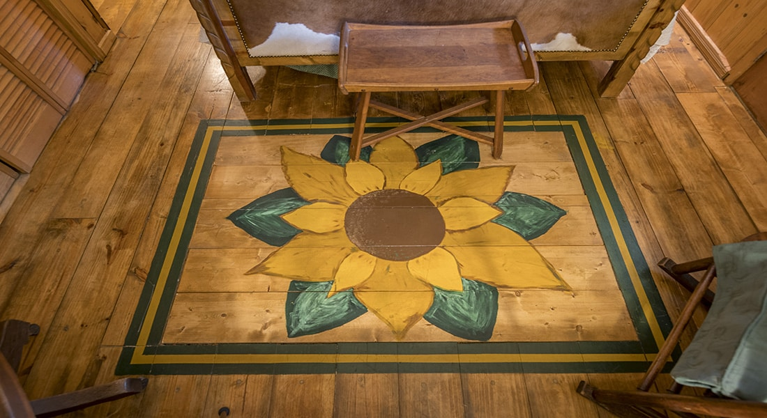 A large yellow and green sunflower is painted on the wooden floor of the bedroom