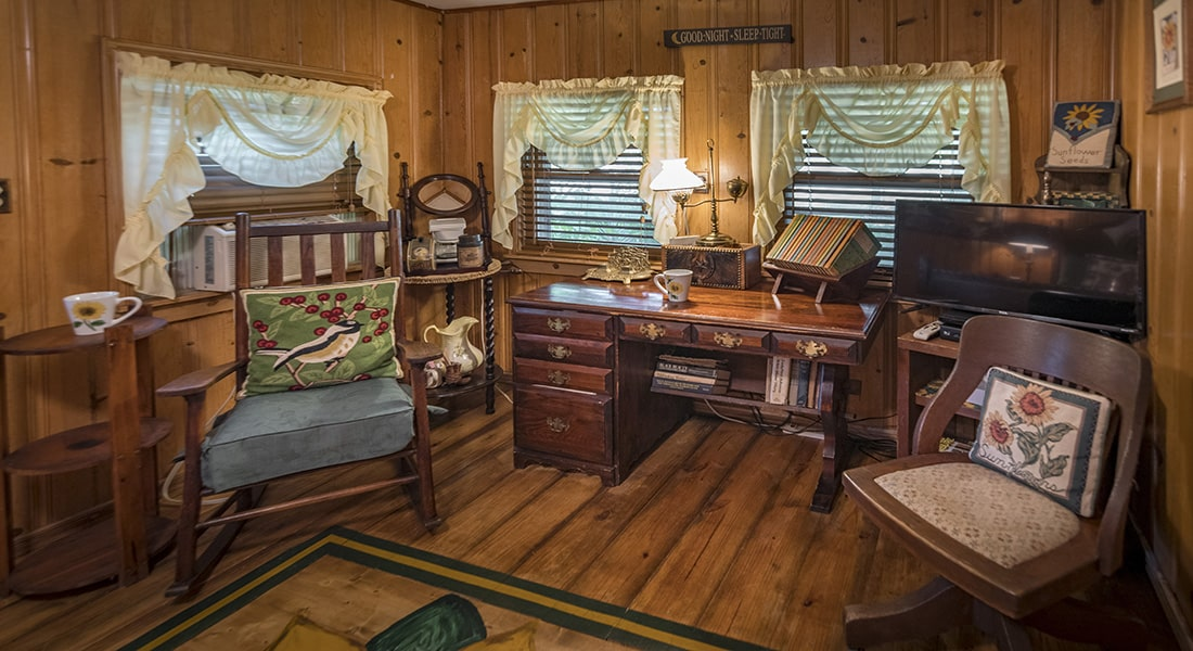 A wooden floor bedroom with an antique desk and rocking chair