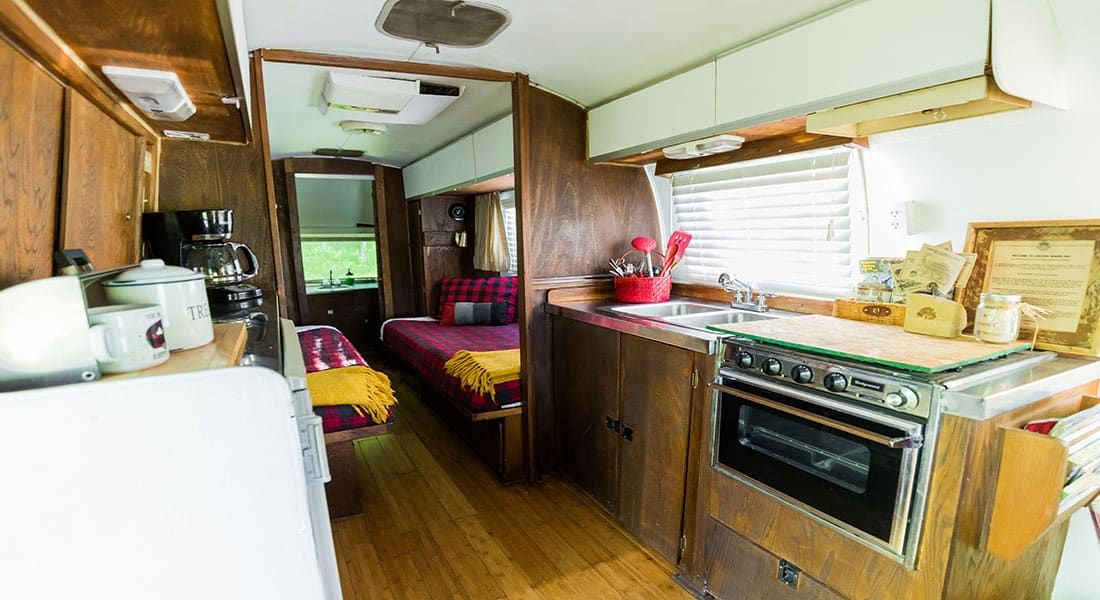 A wooden floor with two twin beds and kitchenette sink