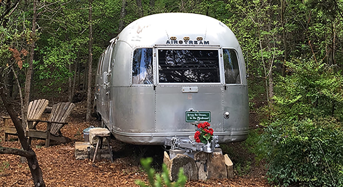 Exterior view of converted Sovereign Airstream trailer in woods with a stone step up.
