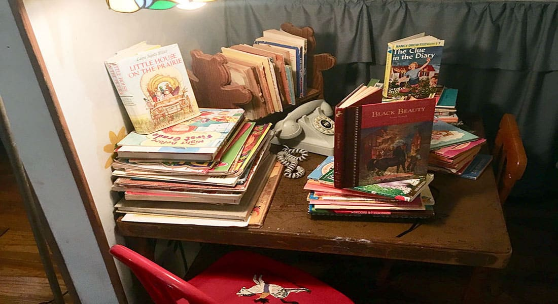 A small table with a kids red chair next to it is covered with children's books.