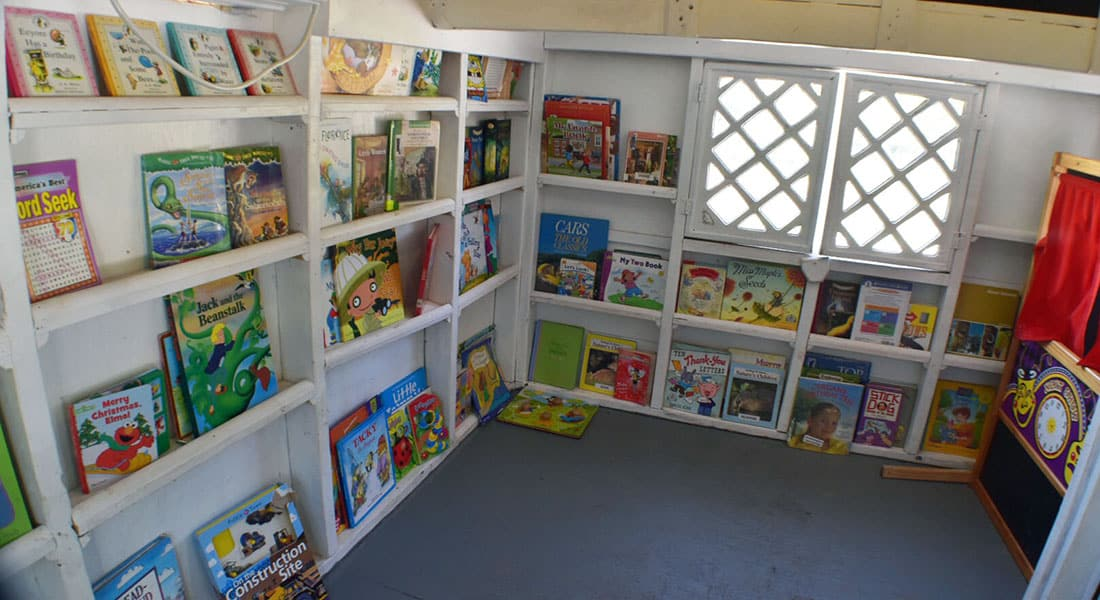 Children's books on white shelves inside a kid's library playhouse