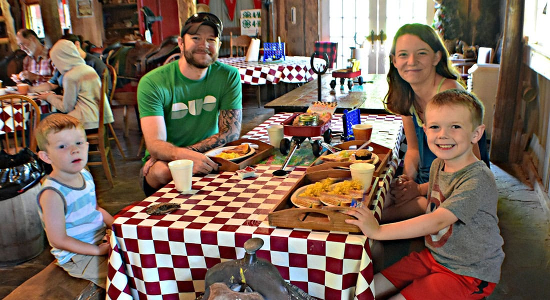 A mom, dad and two sons sit around a red and white checkered table in the breakfast barn eating eggs with a saddle for a seat.