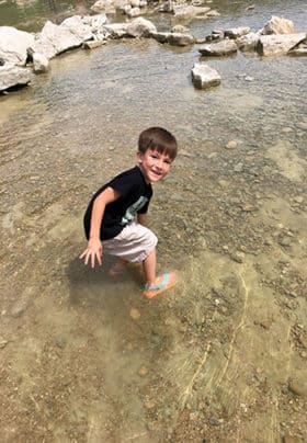 A young boy bends down to feel the dinosaur tracks in the river bed.