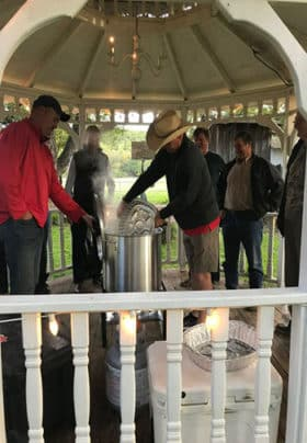 A group of men stand in a gazebo pouring shrimp into a cooker for a shrimp boil.