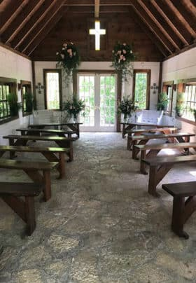Inside of Wedding Chapel Wooden Benches Stained Glass Cross