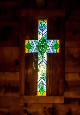 Stained glass cross surrounded by wood siding