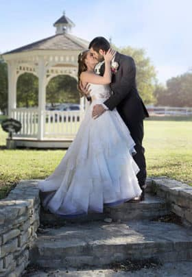 A bride and groom kiss in front of a white gazebo in a green meadow standing on rock steps.