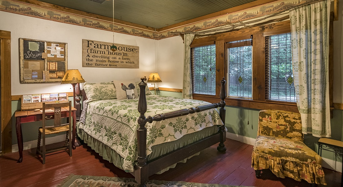 A 4 poster queen bed with quilted spread on burgundy floor with farmhouse decor
