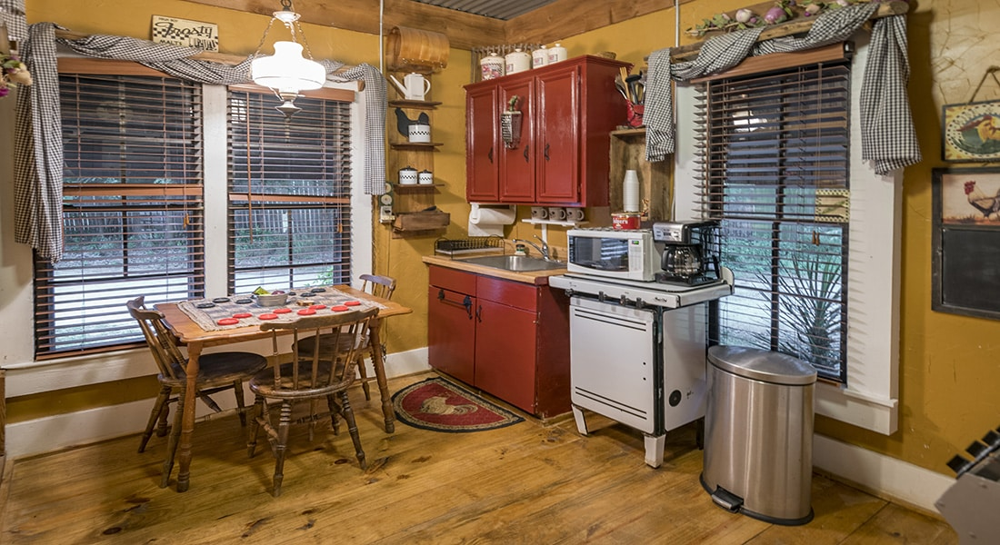 A small table and chairs with checkerboard on top, wooden floor and antique decor in farmhouse kitchen