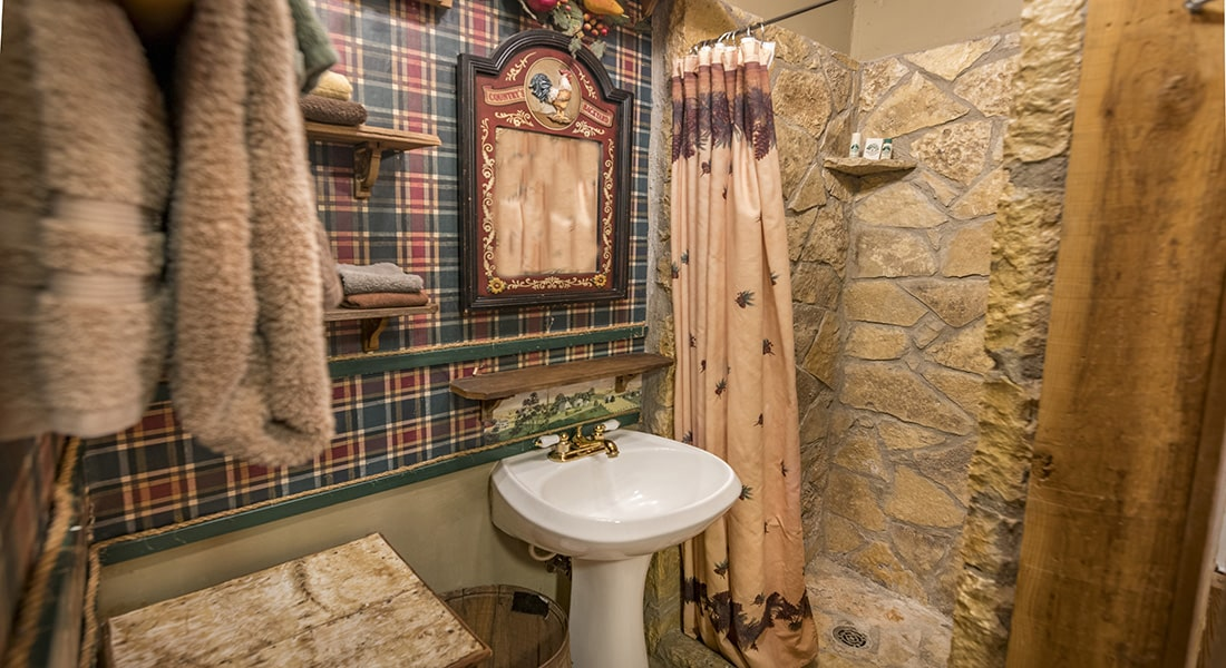 A stone shower with white pedestal sink and farmhouse decor