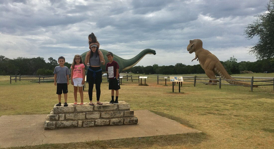 A group of kids stands on a stone plinth in a dinosaur park.