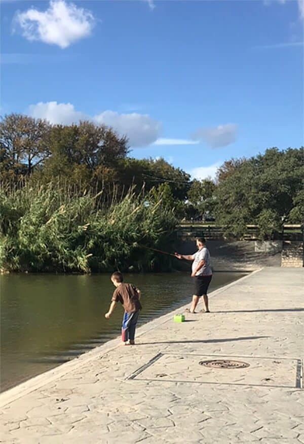 A man and a boy fish in the river ona sunny day.