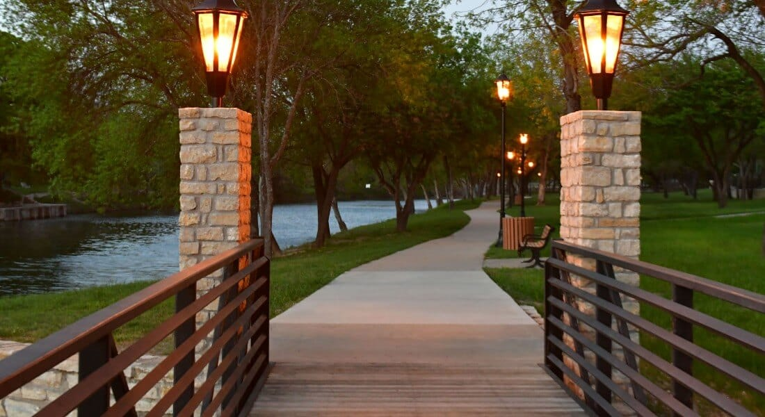 A path lit by carriage lamps along a river at dusk.