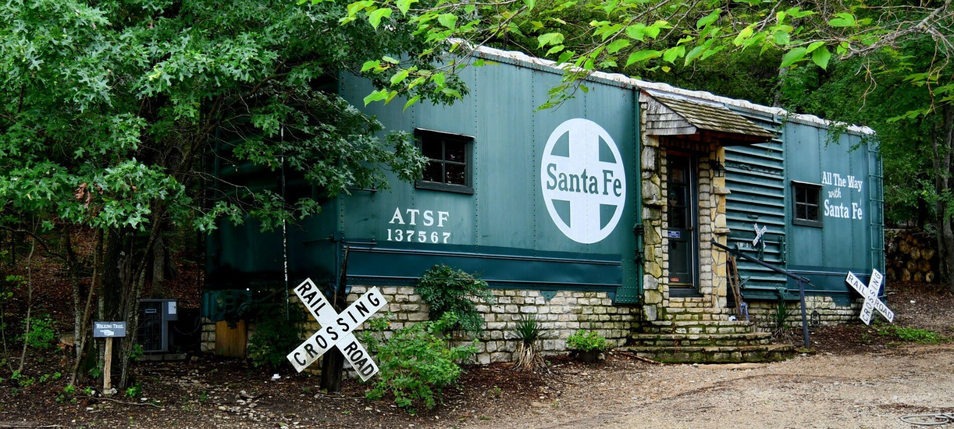 An old green Santa Fe railroad car on a stone foundation with a small stone porch leading to a door.