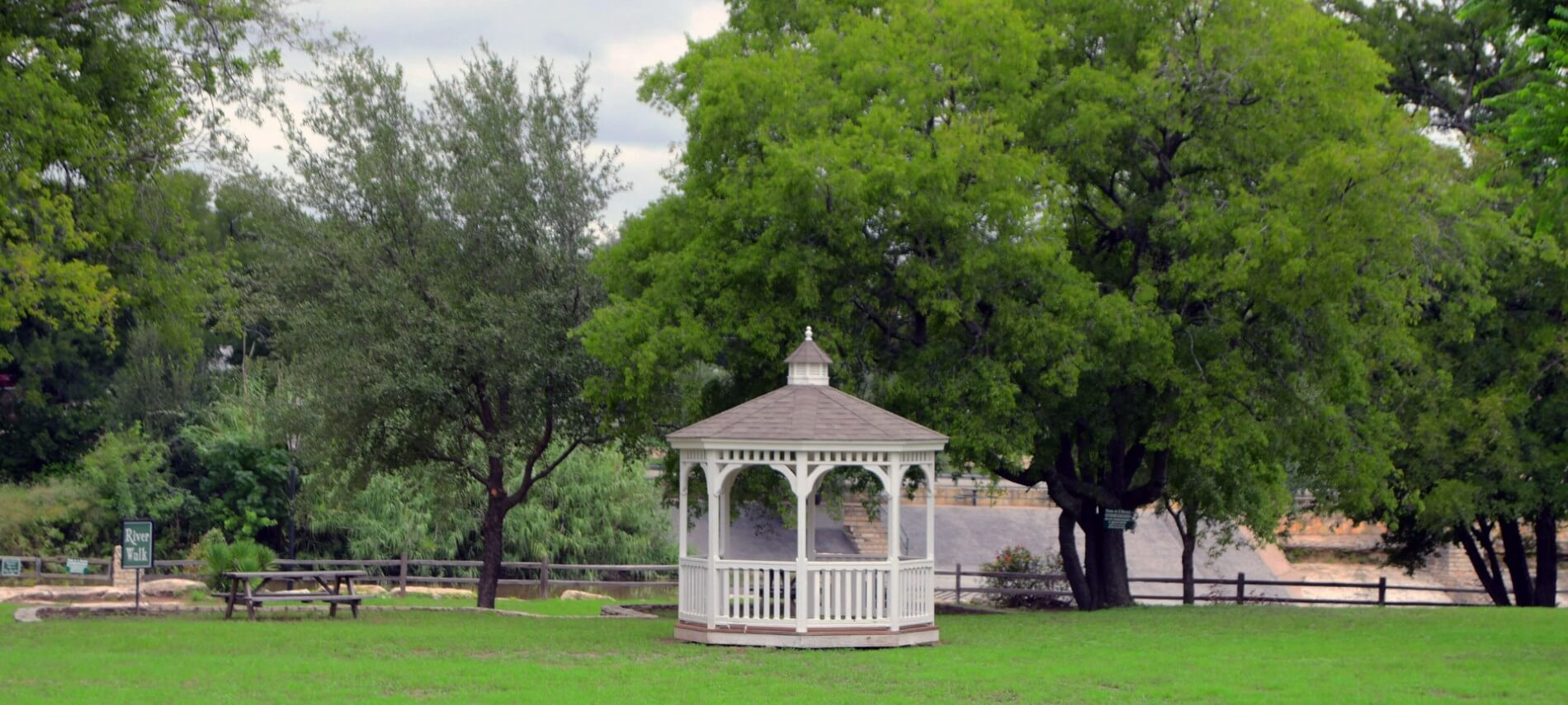 A pretty white gazebo in a green field surrounded by trees.