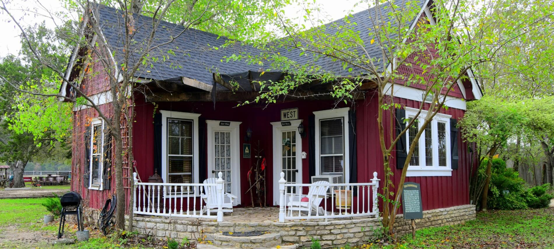 Cute red cabin with black roof and shutters with a stone porch.