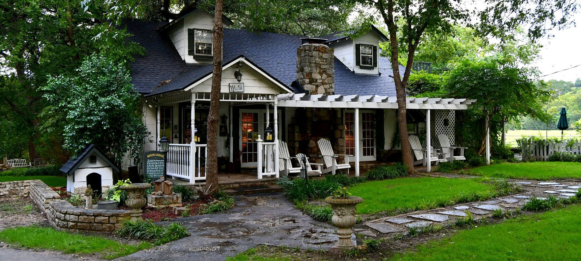 Pretty cabin with a black roof fronted by a stone path and green lawn.
