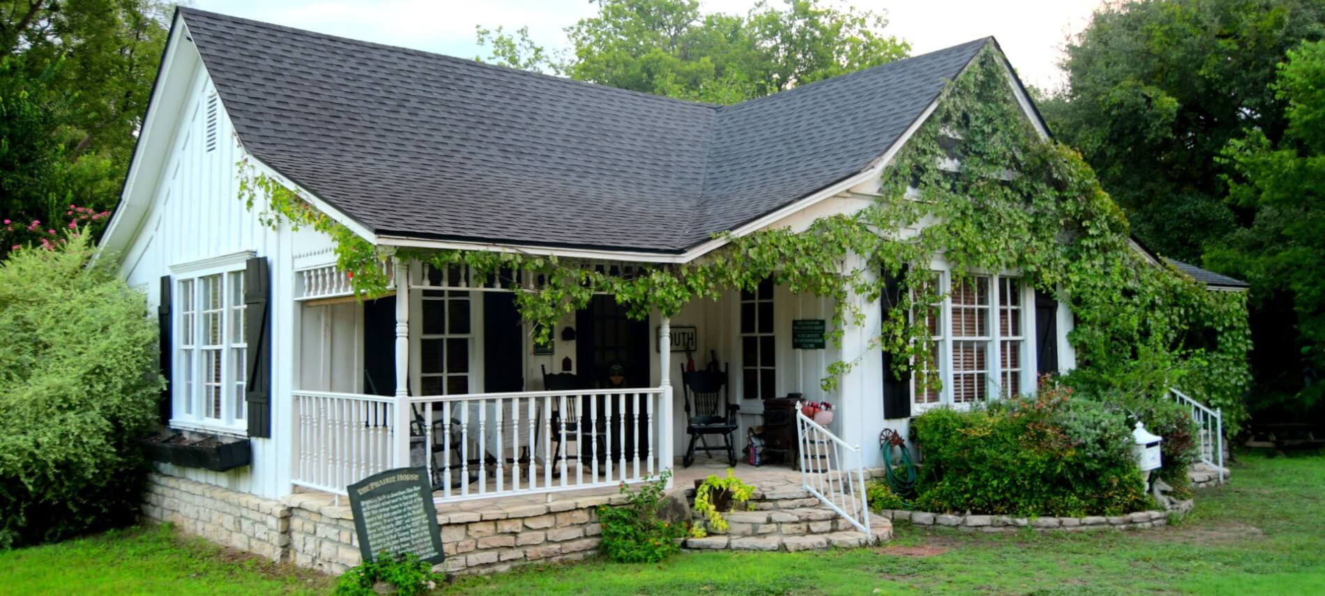 White cabin with roses growing over it and a stone porch.