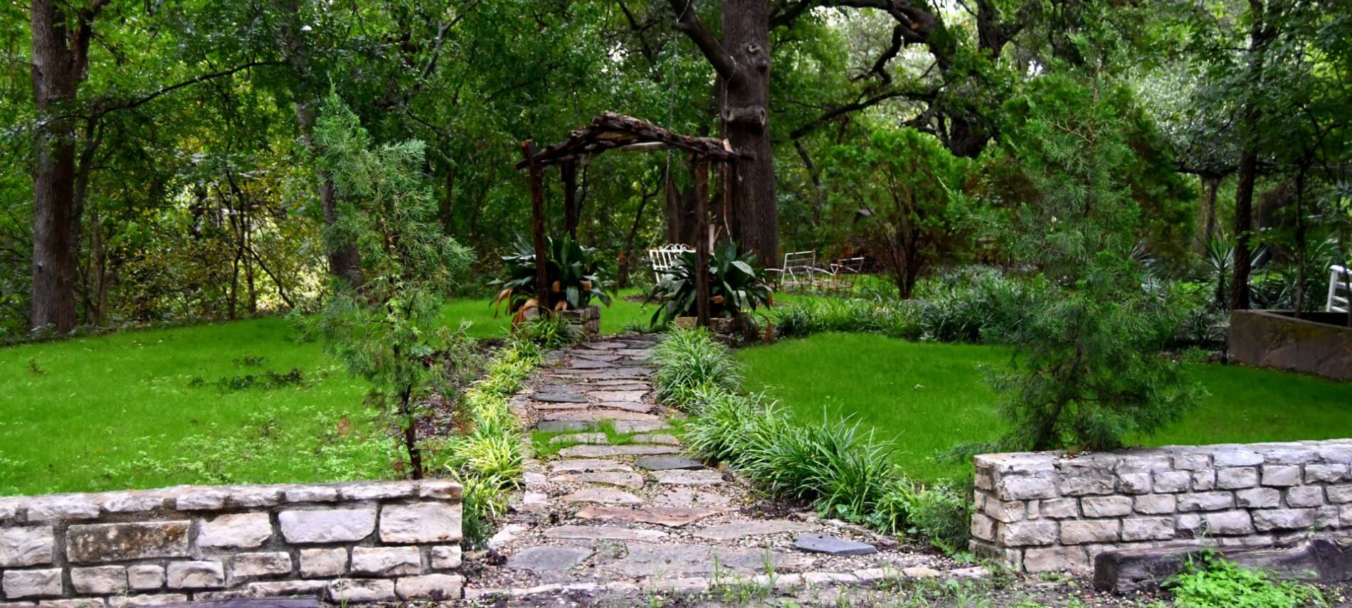 Stone wall and path leading to a wooden swing in a green area.