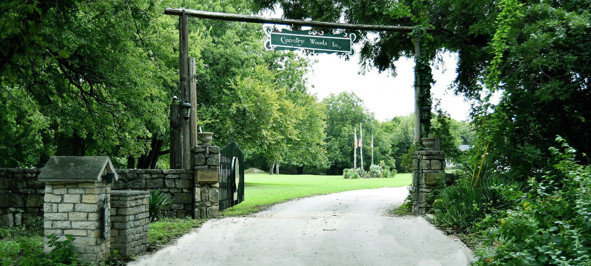 A country road surrounded by green trees leading to a stone entrance with a sign on a tall overhead wooden post.