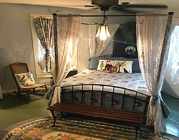 Canopy bed with lace drapes made up in a blue quilt in a bedroom with a large window and rocking chair.
